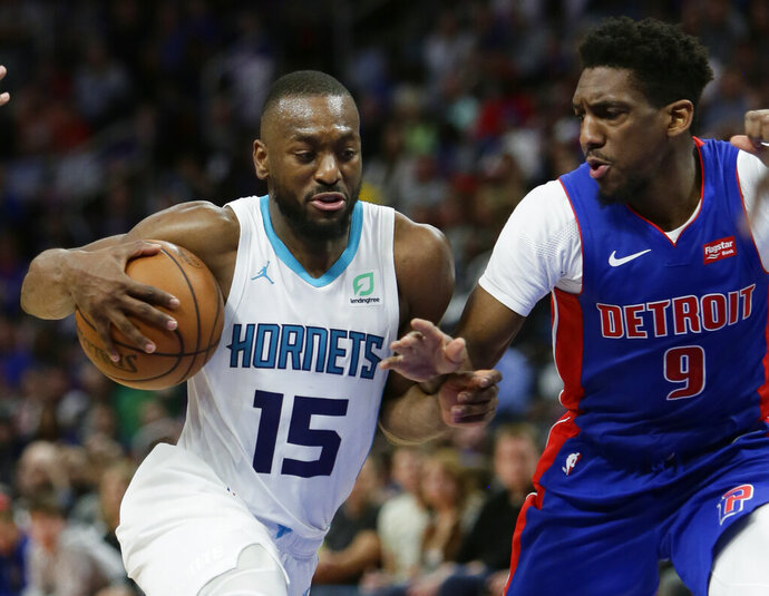 File-This April 7, 2019, file photo shows Charlotte Hornets guard Kemba Walker (15) driving against Detroit Pistons guard Langston Galloway (9) during the second half of an NBA basketball game in Detroit. A person with knowledge of the situation says Kemba Walker has told the Charlotte Hornets of his intention to sign with the Boston Celtics once the NBA's offseason moratorium ends July 6. Walker is planning to meet with the Celtics on Sunday, June 30, 2019, to discuss and likely finalize a four-year, $141 million deal, according to the person who spoke to The Associated Press on condition of anonymity because neither Walker nor the Hornets publicly revealed any details. (AP Photo/Duane Burleson, File)