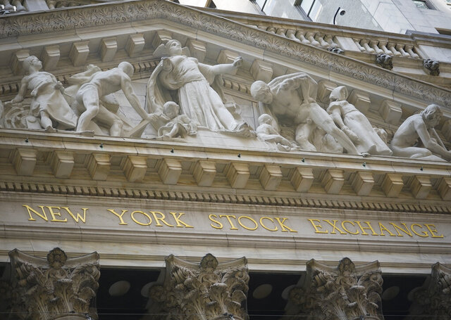 FILE - Marble sculptures occupy the pediment above the New York Stock Exchange signage, Tuesday Aug. 25, 2020, in New York.  Stocks are drifting in mixed trading on Wall Street Friday, Sept. 18, as another zig-zag week for markets closes out following their abrupt loss of momentum this month.(AP Photo/Bebeto Matthews, File)