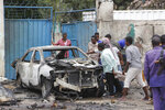 People gather close to the wreckage after a car bomb attack at a Presidential Palace checkpoint in Mogadishu, Somalia, Saturday Sept. 25, 2021. Police said a vehicle laden with explosives rammed into cars and trucks at a checkpoint leading to the entrance of the Presidential Palace, killing at least eight people. (AP Photo/Farah Abdi Warsameh)
