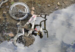 FILE- In this Sept. 26, 2019 file photo, a bicycle that was submerged in a pond lies on a dried-up bank in Helena, Ala. Scientists say more than 45 million people across 14 Southern states are now in the midst of a drought that's cracking farm soil, drying up ponds and raising the risk of wildfires. (AP Photo/Jay Reeves, File)