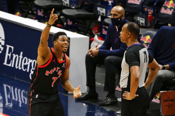 Toronto Raptor guard Kyle Lowry (7) discusses a call with referee Rodney Mott (71) during the first half of an NBA basketball game against New Orleans Pelicans on Saturday, Jan. 2, 2021, in New Orleans. (AP Photo/Butch Dill)