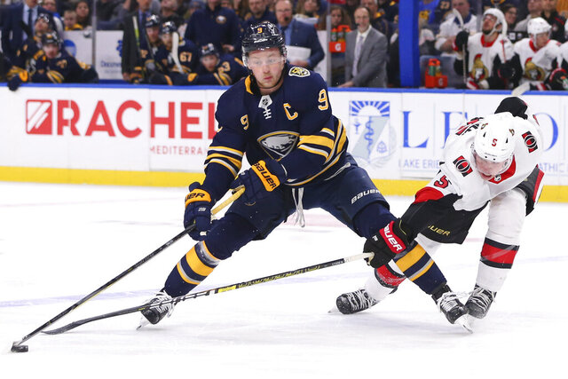 Buffalo Sabres forward Jack Eichel (9) and Ottawa Senators defensemen Mike Reilly (5) compete for the puck during the third period of an NHL hockey game Tuesday, Jan. 28, 2020, in Buffalo, N.Y. (AP Photo/Jeffrey T. Barnes)