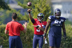 Seattle Seahawks quarterback Russell Wilson (3) passes after taking a snap from center Kyle Fuller, right, during NFL football practice Wednesday, Aug. 25, 2021, in Renton, Wash. (AP Photo/Ted S. Warren)