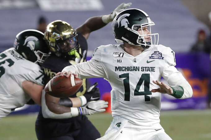 Michigan State's Brian Lewerke (14) throws a pass during the second half of the team's Pinstripe Bowl NCAA college football game against Wake Forest on Friday, Dec. 27, 2019, in New York. Michigan State won 27-21. (AP Photo/Frank Franklin II)