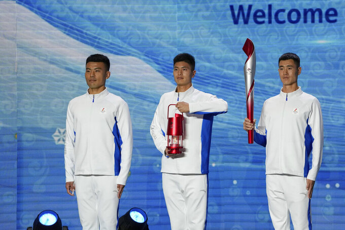 Volunteers hold the Olympic torch and the frame on stage during a welcome ceremony for the Frame of Olympic Winter Games Beijing 2022, held at the Olympic Tower in Beijing, Wednesday, Oct. 20, 2021. A welcome ceremony for the Olympic flame was held in Beijing on Wednesday morning after it arrived at the Chinese capital from Greece. While the flame will be put on display over the next few months, organizers said a three-day torch relay is scheduled starting February 2nd with around 1200 torchbearers in Beijing, Yanqing and Zhangjiakou. (AP Photo/Andy Wong)
