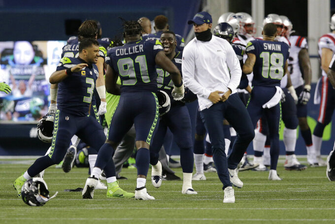 Seattle Seahawks quarterback Russell Wilson (3) celebrates with teammates after the Seahawks beat the New England Patriots 35-30 in an NFL football game, Sunday, Sept. 20, 2020, in Seattle. (AP Photo/John Froschauer)