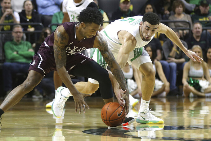 Texas Southern's Justin Hopkins, left, works against Oregon's Chris Duarte for a loose ball during the first half of an NCAA college basketball game in Eugene, Ore., Saturday, Dec. 21, 2019. (AP Photo/Chris Pietsch)