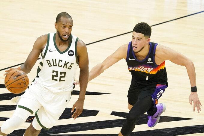 Milwaukee Bucks forward Khris Middleton (22) drives against Phoenix Suns guard Devin Booker during the second half of Game 5 of basketball's NBA Finals, Saturday, July 17, 2021, in Phoenix. (AP Photo/Matt York)