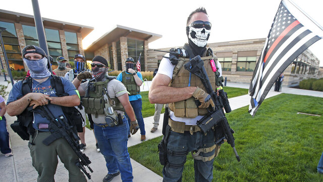 People carry weapons outside the Cottonwood Heights Police Department on Monday, Aug. 3, 2020, in Cottonwood Heights, Utah. Groups of dueling protesters faced off outside the suburban Salt Lake City police department in response to use of force by officers at a protest the night before that resulted in the arrest of eight people. (AP Photo/Rick Bowmer)