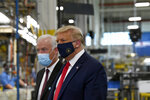 President Donald Trump wears a mask as he gets a tour of the Whirlpool Corporation facility from Jim Keppler, Vice President, Integrated Supply Chain and Quality, Whirlpool Corporation in Clyde, Ohio, Thursday, Aug. 6, 2020. Trump is in Ohio to promote the economic prosperity that much of the nation enjoyed before the coronavirus pandemic and try to make the case that he is best suited to rebuild a crippled economy. (AP Photo/Susan Walsh)