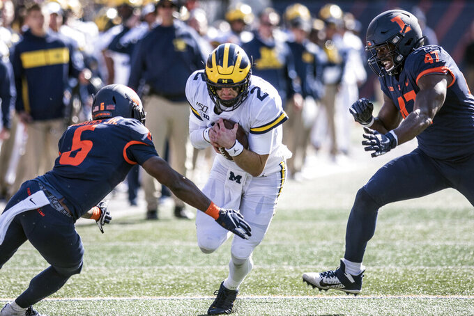 Michigan's Shea Patterson runs the ball as Illinois' Tony Adams (6) and Oluwole Betiku, Jr. (47) close in during the second half of an NCAA college football game, Saturday, Oct.12, 2019, in Champaign, Ill. (AP Photo/Holly Hart)