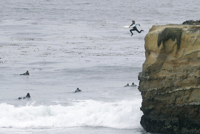 A surfer jumps off a cliff into the water during the coronavirus outbreak in Santa Cruz, Calif., Thursday, July 2, 2020. Californians are being wooed by local tourism boards promising safe and clean lodging, dining and sightseeing in a bid to boost the state's devastated economy. Visitors bureaus in Sonoma, Santa Cruz, Monterey and greater Palm Springs are among those pitching local travel with messages to wear masks and to practice social distancing. (AP Photo/Jeff Chiu)