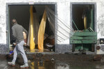 A man walks past a house wrecked by the weather in Horta, in the Portuguese island of Faial, Wednesday, Oct. 2, 2019. Hurricane Lorenzo powered across the Atlantic Ocean on Wednesday, lashing the Azores archipelago with heavy rains, powerful winds and high waves and significantly damaging one island's main port. (AP Photo/Joao Henriques)