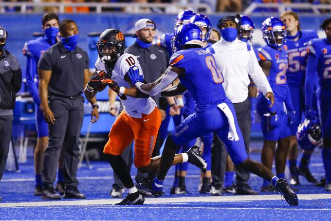 Oklahoma State wide receiver Rashod Owens (10) is pushed out of bounds by Boise State safety JL Skinner (0) during the second half of an NCAA college football game Saturday, Sept. 18, 2021, in Boise, Idaho. (AP Photo/Steve Conner)