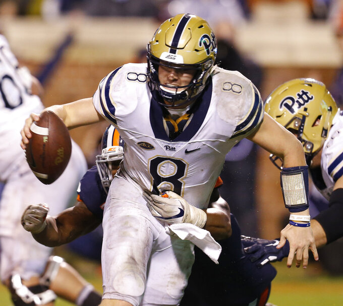 Pittsburgh quarterback Kenny Pickett (8) slips the tackle of Virginia linebacker Chris Peace, background, during the second half of an NCAA college football game in Charlottesville, Va., Friday, Nov. 2, 2018. (AP Photo/Steve Helber)