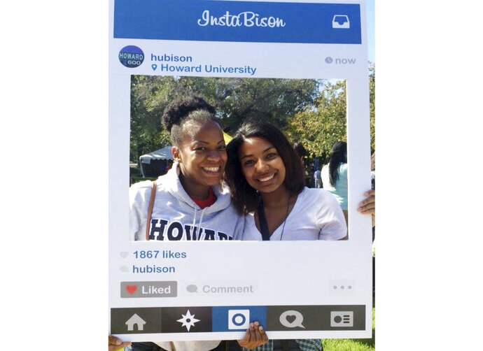 In this October 2014 photo provided by Nerdwallet, Takiia Anderson, left, poses for a photo with her daughter Taje Perkins during a campus visit to Anderson's alma mater, Howard University in Washington. Today, Anderson's student debt is long gone. She has nearly $500,000 in retirement savings, and her daughter, Taje Perkins, finished her third year at Spelman College in Atlanta with no student loans to cover its nearly $30,000 per year in tuition and fees. (Nerdwallet via AP)