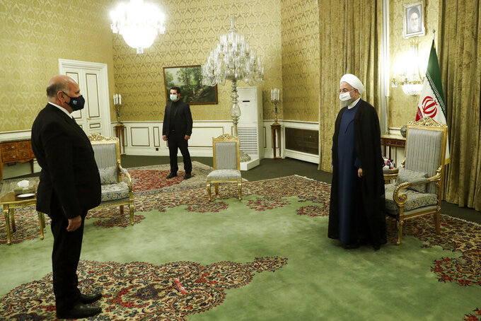 In this photo released by the official website of the office of the Iranian Presidency, President Hassan Rouhani, right, welcomes Iraqi Foreign Minister Fuad Hussein for their meeting, in Tehran, Iran, Saturday, Sept. 26, 2020. (Iranian Presidency Office via AP)