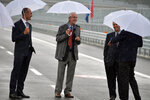 Renzo Piano, center, walks along the new San Giorgio Bridge in Genoa, Italy, Monday, Aug. 3, 2020. Two years ago this month, a stretch of roadbed collapsed on Genoa's Morandi Bridge, sending cars and trucks plunging to dry riverbed below and ending 43 lives. On Monday, Italy's president journeys to Genoa for a ceremony to inaugurate a replacement bridge. Designing the new span was Genoa native, Renzo Piano, a renowned architect. (Gian Mattia D'Alberto/LaPresse via AP)