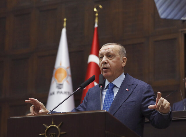 Turkish President Recep Tayyip Erdogan addresses the members of his ruling party in Parliament, in Ankara, Turkey, Wednesday, March 11, 2020. Erdogan vowed on Wednesday to respond with greater military force to action by Syria's government that would break a fragile cease-fire in Syria's northwestern Idlib province, that was brokered last week. (AP Photo/Burhan Ozbilici)