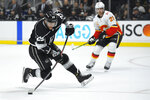 Los Angeles Kings right wing Marin Frk, left, shoots the puck as Calgary Flames center Elias Lindholm watches during the second period of an NHL hockey game Wednesday, Feb. 12, 2020, in Los Angeles. (AP Photo/Mark J. Terrill)