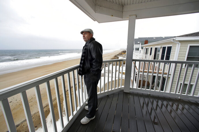 In this Feb. 15, 2019 photo, real estate agent Tom Saab stands on a oceanfront deck at a condo he developed in Salisbury, Mass. Academic researchers say concerns over rising sea levels and increased flooding are having subtle but significant impacts on coastal property values, finding that climate change concerns have sapped more than $15 billion in appreciation from homes along the Eastern Seaboard and Gulf Coast. (AP Photo/Elise Amendola)