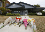 FILE - In this Monday, Oct. 14, 2019 photo, flowers lie on the sidewalk in front of the house in Fort Worth, Texas, where a white Fort Worth police officer Aaron Dean shot and killed Atatiana Jefferson, a black woman, through a back window of her home. Dean was not heard identifying himself as police on the bodycam video, and Interim Police Chief Ed Kraus has said there was no sign Dean or the other officer who responded even knocked on the front door. Dean resigned before being charged with murder Monday. (AP Photo/David Kent, File)
