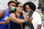 FILE— In this June 18, 2021 file photograph, Boston's acting Mayor Kim Janey, right, takes a selfie with attendees as she meets people in Boston's Nubian Square for a Juneteenth commemoration. With Boston's preliminary mayoral election just a month off, voters are on the verge of making a historic decision by narrowing the field of five major candidates, all of whom are people of color. Since it first started electing mayors nearly 200 years ago, Boston has only tapped white men to lead the city — a streak certain to end this year, a reflection in part of the city's changing demographics. (AP Photo/Elise Amendola, File)