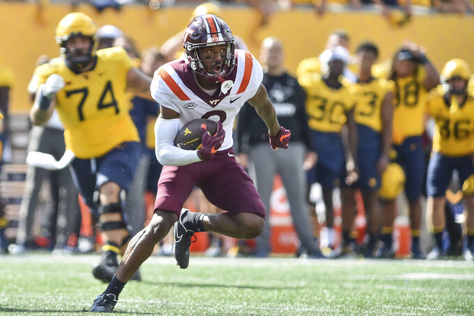 Virginia Tech defensive back Jermaine Waller (2) returns an interception late in the second half of an NCAA college football game against West Virginia in Morgantown, W.Va., Saturday, Sept. 18, 2021.  (AP Photo/William Wotring)
