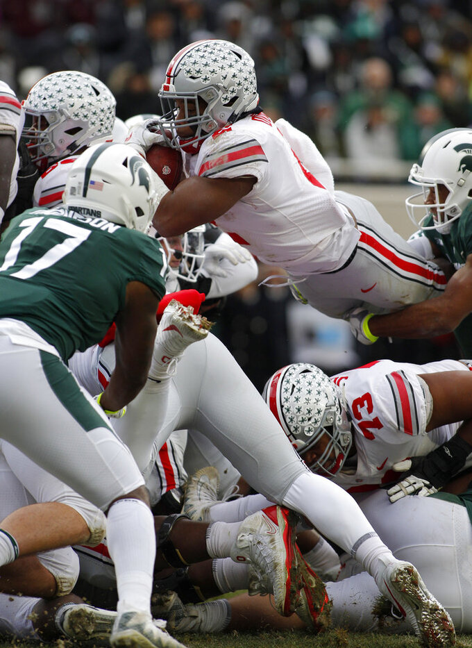 Ohio State's J.K. Dobbins, top center, dives over teammate Michael Jordan (73) against Michigan State's Tyriq Thompson (17) and Khari Willis, right, during the second quarter of an NCAA college football game, Saturday, Nov. 10, 2018, in East Lansing, Mich. (AP Photo/Al Goldis)