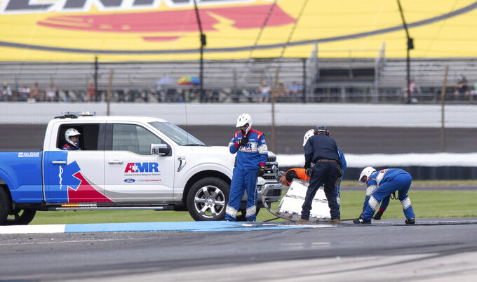 Members of the track crew remove car parts of Aric Almirola at a curb that had been repaired earlier in the race during a NASCAR Cup Series auto race at Indianapolis Motor Speedway, Sunday, Aug. 15, 2021, in Indianapolis. (AP Photo/Doug McSchooler)