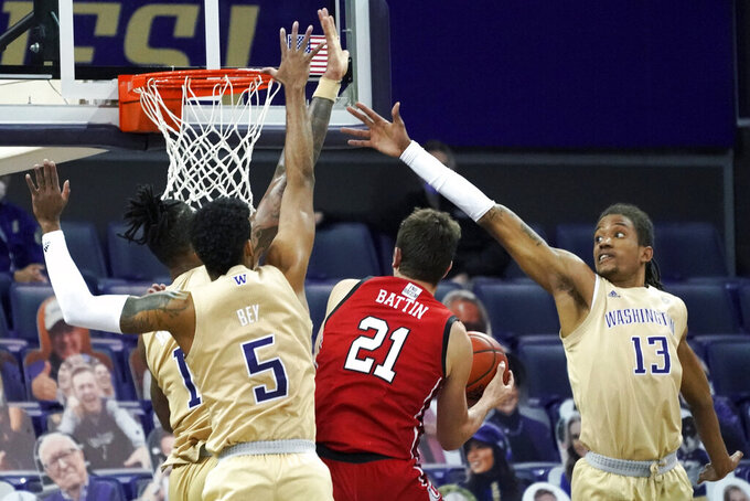 Washington forward Hameir Wright (13) and guard Jamal Bey (5) try to block a shot by Utah forward Riley Battin (21) during the first half of an NCAA college basketball game, Sunday, Jan. 24, 2021, in Seattle. (AP Photo/Ted S. Warren)