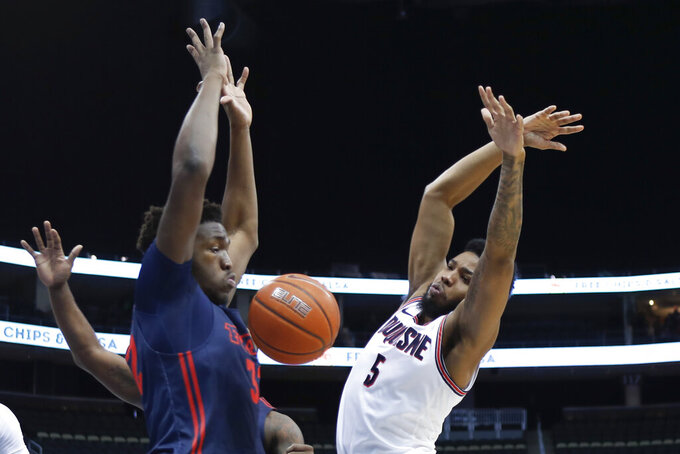 The ball pops loose as Duquesne's Marcus Weathers (5) tries to shoot as Dayton's Jordy Tshimanga (32) defends during the first half of an NCAA college basketball game Wednesday, Jan. 29, 2020, in Pittsburgh. (AP Photo/Keith Srakocic)