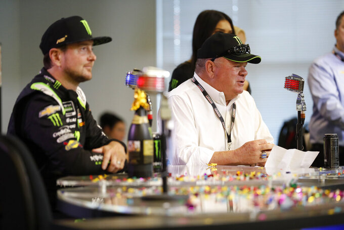 Kurt Busch, left, listens as team owner Chip Ganassi, right, responds to questions during a news conference after announcing that Busch had been given a multi-year contract wth Ganassi Racing at Texas Motor Speedway in Fort Worth, Texas, Friday, Nov. 2, 2019. (AP Photo/Roger Steinman)