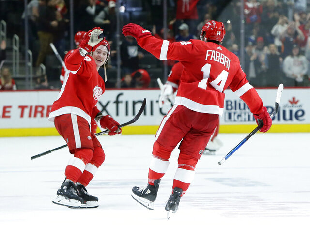 Detroit Red Wings center Robby Fabbri (14) celebrates with Red Wings left wing Tyler Bertuzzi, left, after scoring to win the shootout 2-1 against the Tampa Bay Lightning in NHL hockey game Sunday, March 8, 2020, in Detroit. The Red Wings defeated Tampa 5-4. (AP Photo/Duane Burleson)