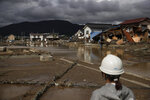 A woman looks at homes devastated by Typhoon Hagibis Tuesday, Oct. 15, 2019, in Nagano, Japan. More victims and more damage have been found in typhoon-hit areas of central and northern Japan, where rescue crews are searching for people still missing. (AP Photo/Jae C. Hong)
