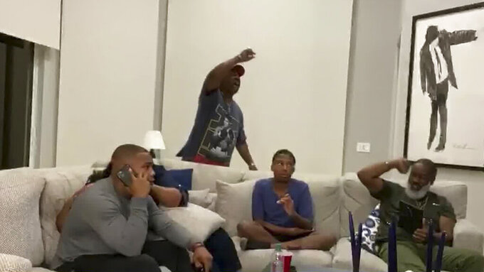 In this still image from video provided by the NFL, J.K Dobbins, left, talks on the phone as he's selected by the Baltimore Ravens during the second round of the NFL football draft, Friday, April 24, 2020. (NFL via AP)