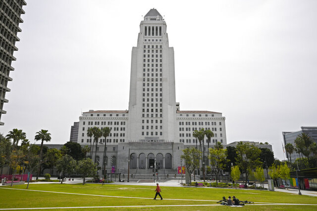A few people use Grand Park at the foot of Los Angeles City Hall, Tuesday, March 31, 2020, in Los Angeles. The new coronavirus causes mild or moderate symptoms for most people, but for some, especially older adults and people with existing health problems, it can cause more severe illness or death. (AP Photo/Mark J. Terrill)