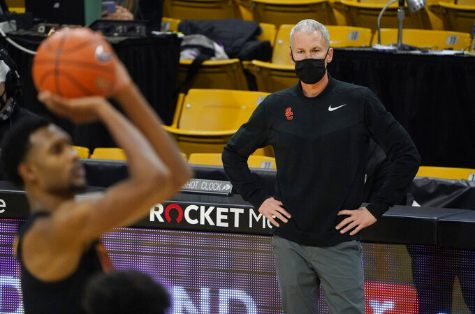 FILE - In this Thursday, Feb. 25, 2021 file photo, Southern California head coach Andy Enfield, back, looks on as Southern California forward Isaiah Mobley shoots a free throw in the second half of an NCAA college basketball game against Colorado in Boulder, Colo. . (AP Photo/David Zalubowski, File)