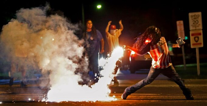FILE - In this Aug. 13, 2014, file photo Edward Crawford Jr., returns a tear gas canister fired by police who were trying to disperse protesters in Ferguson, Mo. Three journalists with Al Jazeera America who were tear-gassed during a protest in Ferguson, after Michael Brown's death in 2014 have settled a lawsuit with the county whose SWAT team fired the tear gas. St. Charles County agreed to pay $280,000, according to the law firm that represented the journalists.(Robert Cohen/St. Louis Post-Dispatch via AP)