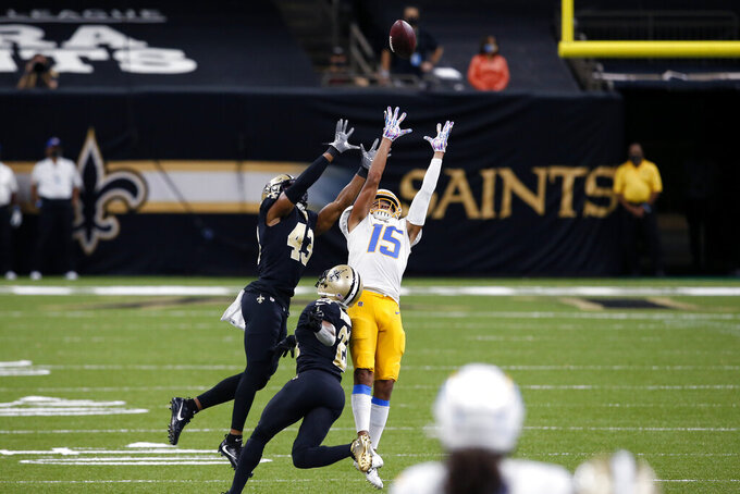 Los Angeles Chargers wide receiver Jalen Guyton (15) leaps for a pass against New Orleans Saints free safety Marcus Williams (43) in the first half of an NFL football game in New Orleans, Monday, Oct. 12, 2020. (AP Photo/Butch Dill)