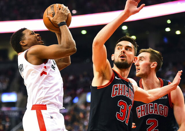 Toronto Raptors guard Kyle Lowry (7) looks to shoot as Chicago Bulls guard Tomas Satoransky (31) and Luke Kornet (2) look on during first-half NBA basketball game action in Toronto, Sunday, Feb. 2, 2020. (Frank Gunn/The Canadian Press via AP)