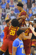 Southern California guard Tahj Eaddy, top, celebrates with teammates as UCLA guard Jaylen Clark, left, walks off the court after Eaddy hit a game-winning three-point shot during the second half of an NCAA college basketball game Saturday, March 6, 2021, in Los Angeles. USC won 64-63. (AP Photo/Mark J. Terrill)