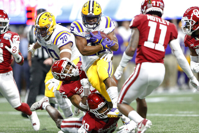 LSU running back Clyde Edwards-Helaire (22) runs through attempted tackles by Oklahoma safeties Pat Fields (10) and Justin Broiles (25) during the first half of the Peach Bowl NCAA college football playoff semifinal in Atlanta on Saturday, Dec. 28, 2019. (Ian Maule/Tulsa World via AP)