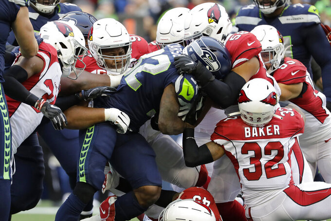 Seattle Seahawks running back Chris Carson (32) is tackled by Arizona Cardinals strong safety Budda Baker (32) and middle linebacker Jordan Hicks (58) during the first half of an NFL football game, Sunday, Dec. 22, 2019, in Seattle. (AP Photo/Lindsey Wasson)