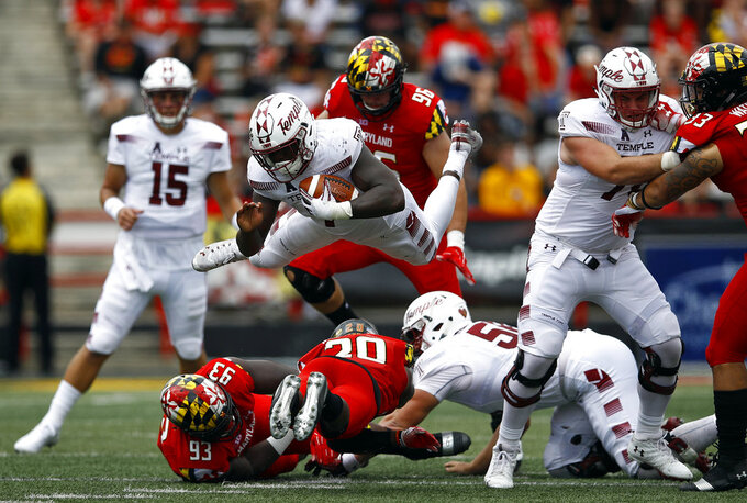 Temple running back Ryquell Armstead, center, leaps over Maryland defensive lineman Oseh Saine (93) and defensive back Antwaine Richardson (20) as he rushes the ball in the second half of an NCAA college football game, Saturday, Sept. 15, 2018, in College Park, Md. Temple won 35-14. (AP Photo/Patrick Semansky)