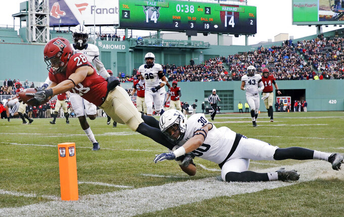 """FILE - In this Nov. 17, 2018, file photo, Harvard wide receiver Henry Taylor (28) stretches for a touchdown against Yale linebacker Noah Pope (30) during the first half of an NCAA college football game at Fenway Park in Boston. All eight Ivies are requiring that their football teams be vaccinated for COVID-19 — just like the rest of the students on campus. Ivy League executive director Robin Harris said this month that the goal had been reached with """"very limited medical or religious"""" exceptions. (AP Photo/Charles Krupa, File)"""