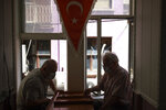 People play cards in a coffee shop in Istanbul, Thave fun in a restaurant in Istanbul, Thursday, July 1, 2021. Turkey's government  on Thursday eased restrictions in place to curb the spread of the coronavirus, and have reopened theaters, cinemas and other entertainment centers. (AP Photo/Emrah Gurel)