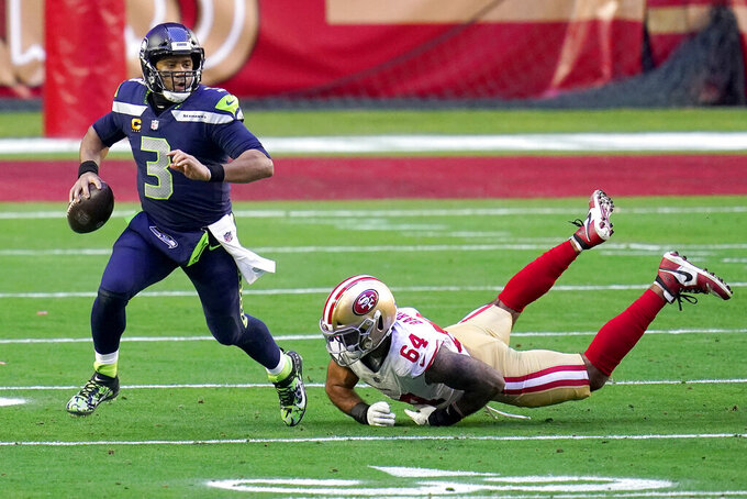 Seattle Seahawks quarterback Russell Wilson (3) scrambles as San Francisco 49ers defensive end Alex Barrett (64) defends during the first half of an NFL football game, Sunday, Jan. 3, 2021, in Glendale, Ariz. (AP Photo/Ross D. Franklin)
