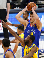 Denver Nuggets center Nikola Jokic, back, looks to pass the ball as Golden State Warriors forward Andrew Wiggins defends in the first half of an NBA basketball game, Thursday, Jan. 14, 2021, in Denver. (AP Photo/David Zalubowski)