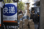 ADDS TRANSLATION - Delivery men wait to distribute parcels on the streets of Beijing on Monday, Nov. 11, 2019. Chinese e-commerce giants Alibaba and JD.com reported a total of more than $50 billion in sales on Monday in the first half of Singles Day, an annual marketing event that is the world's busiest online shopping day. The sign reads